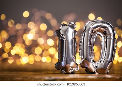 Silver number 10 celebration foil balloon against blurred light background