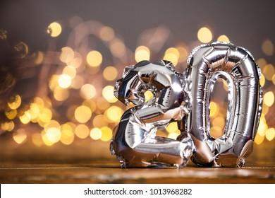 Silver Number 20 Celebration Foil Balloon Against Blurred Light Background