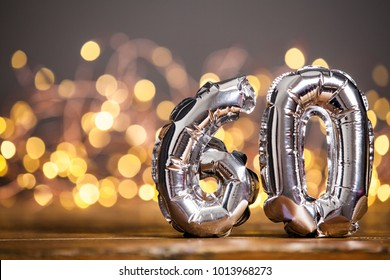 Silver number 60 celebration foil balloon against blurred light background