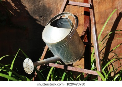 Silver ornamental water bucket mounted on iron bracket in garden
