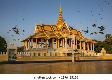Silver Pagoda and Royal Palace in Phnom Penh, Cambodia at sunset with flock of birds in flight