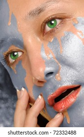 Silver paint washing out of  woman face revealing clean skin
