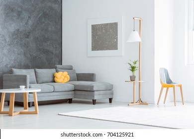 Silver painting above grey couch set with yellow pillow in spacious living room with contrast walls