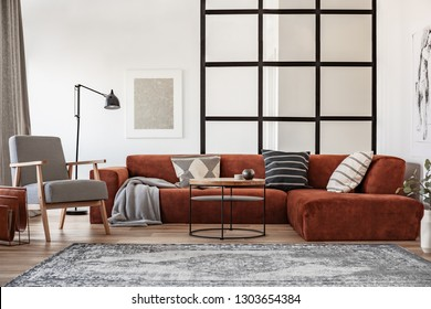 Silver painting on white wall of elegant living room interior with brown corner sofa with pillows
