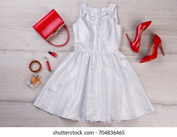 Silver party dress on wooden background. Fashion cocktail dress, red heels and handbag clutch, cosmetics, top view.