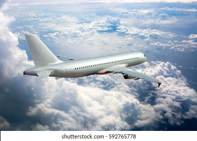 Silver passenger jet plane in the blue sky. Aircraft flying high through the cumulus clouds. Airplane back view.