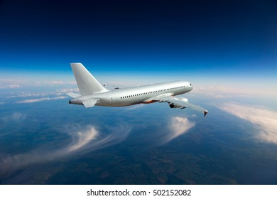 A silver passenger plane in the sky. Aircraft flying high above the blue Earth.