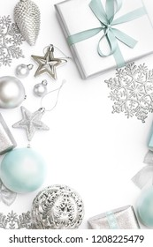 Silver and pastel blue christmas gifts, ornaments and decorations isolated on white background. Wrapped xmas boxes, christmas ornaments and baubles. Christmas border.