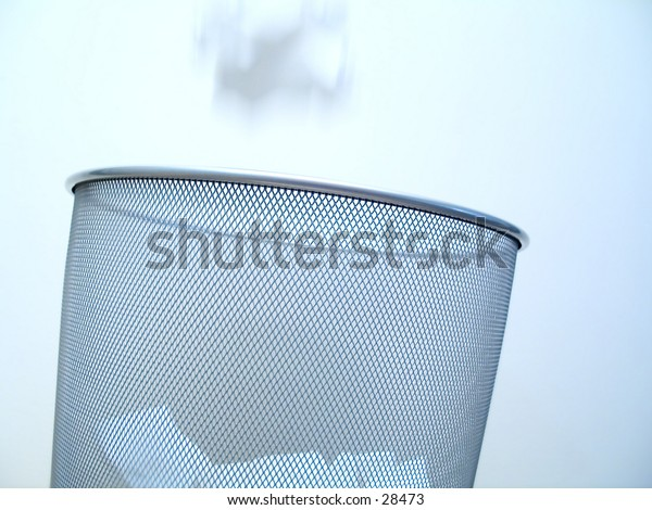 A silver pattered garbabe can close up filled with white balls of paper. A ball of paper is falling into the can (motion blur)