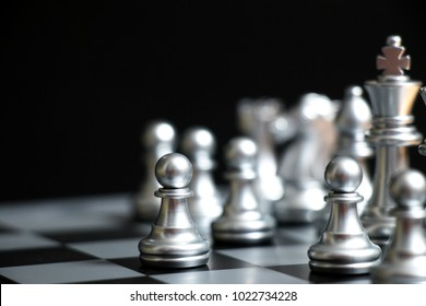 Silver pawn is on the first move in chess game on black background (Concept for business decision, start or beginning project)