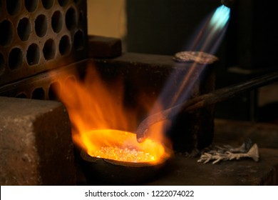 Silver pellets being melted in a red hot melting pot with a blowtorch, producing beautiful orange flames