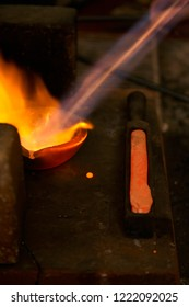 Silver pellets remains being melted in a red hot melting pot with a blowtorch after casting a still hot silver ingot, with beautiful orange flames