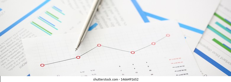 Silver pen lie on paper chart with financial insurance statistic. Tax business report concept.