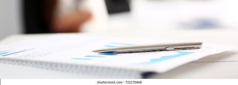 Silver pen lying on important paper at table with people in background in office closeup. Trade result form, paperwork job, bank credit, loan balance, invest payment, irs currency audit, budget trend