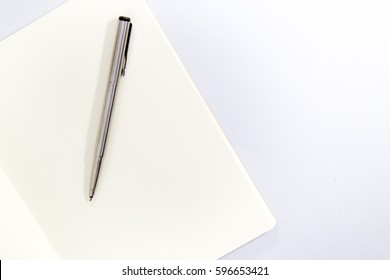 silver pen and notebook on white background