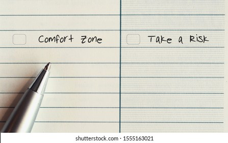A silver pen on a line note paper with two choices to choose between COMFORT ZONE  and  TAKE A RISK - concept of making serious decision to step out from fear and start new thing