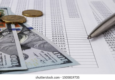 A silver pen and US dolar money and coins for financial and business concepts, lie on a table with tables of numbers. Banking, investments, deposits, save money.Blur background