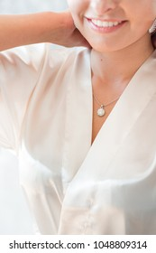 Silver pendant being put on a neck by a smiling beautiful woman