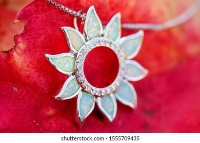 Silver pendant with white opal mineral stone on autumn background
