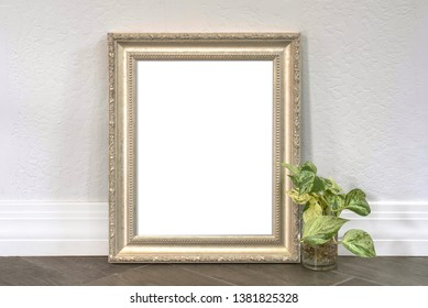 Silver pewter 8x10 picture frame with a philodendron plant on a wood textured tiled floor.  For mocking up photos and messages.