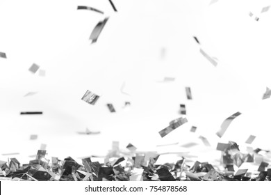 Silver pieces of falling confetti on white
