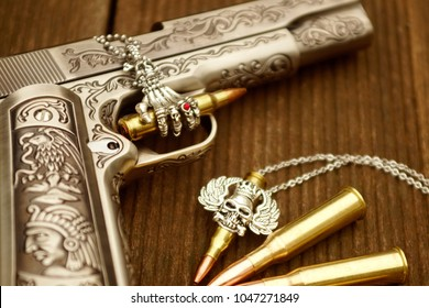 Silver pistol engraved in floral textures. There are golden bulets, ammo on the wooden background, as well as a skull wings necklace and a skul hand necklace.
