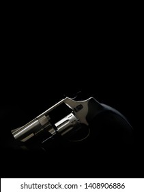 Silver pistol revolver on a black background. Low key photography. Weapon concept. Background for gun postcard.