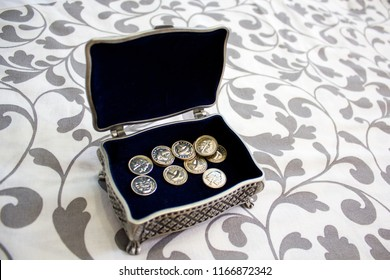 Silver plated box with silver wedding coins with the lid open on a white mat with prints on plants