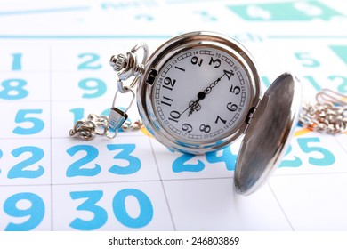 Silver pocket clock on calendar background