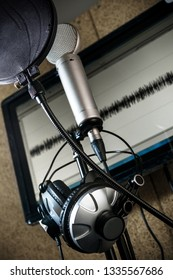 SILVER PROFESSIONAL MICROPHONE WITH HEADPHONES AND A SOFLER MONITOR IN RECORDING STUDIO
