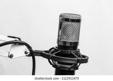 Silver professional studio condenser microphone in the anti vibration holder protrudes from the bottom of the screen isolated on white background