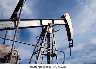 silver pump jack in crude oil field mine
