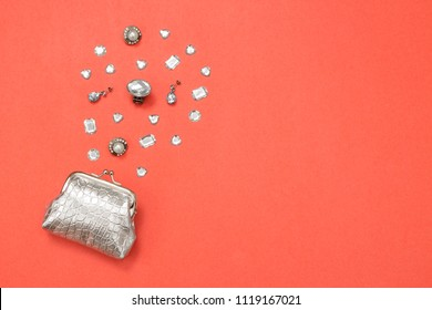 Silver purse, gems and jewelry on vibrant pink background with copy space.