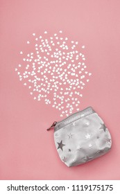 Silver purse and shiny hearts, on pastel pink background.