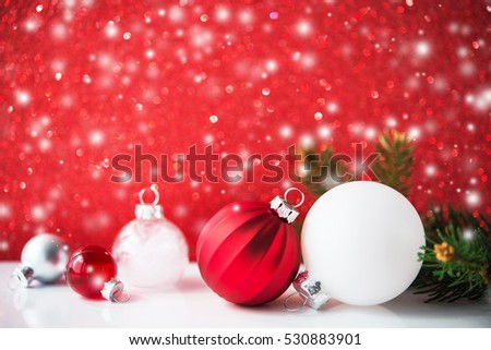 silver red and white christmas ornaments on red glitter bokeh background with blurred snow and