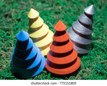 Silver, red, yellow and blue wooden Christmas trees on mossy background