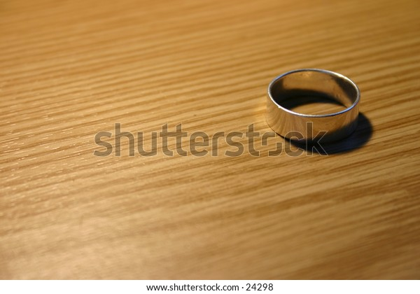 Silver ring against wooden plate.