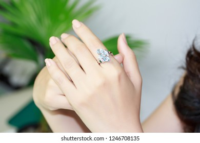 Silver ring with blue topaz gemstone on female's finger