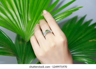 Silver ring with a precious stone peridot ring finger on a beautiful female hand
