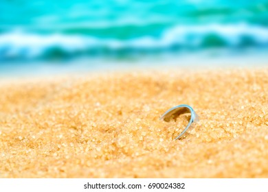 Silver ring in the sand on the background of beach and sea