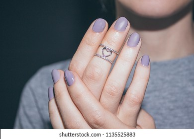 Silver ring in the shape of the heart on the phalanx of the finger. Macro