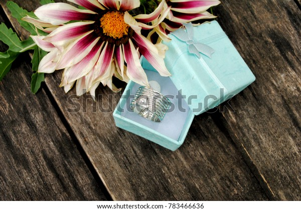 Silver ring with triangle pattern laying near white and pink camomile flowers on old wooden grey table