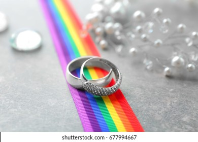 Silver rings for lesbian wedding and rainbow ribbon on gray table