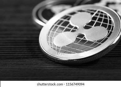 silver ripple coins on a black wood background