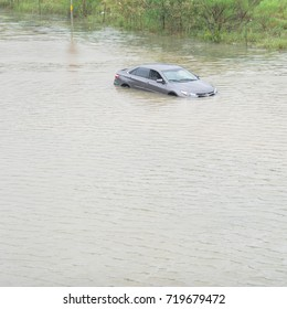 Silver sedan car swamped by flood water in East Houston, Texas, US by Harvey Tropical Storm. Submerged car on deep heavy high water road. Disaster Motor Vehicle Insurance Claim Themed. Severe weather