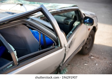 Silver sedan car written off in a traffic accident standing in the road surrounded by shattered glass from its destroyed windscreen and windows, with a flattened roof and crumpled coachwork