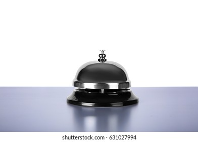 Silver service bell on desk, isolated on white