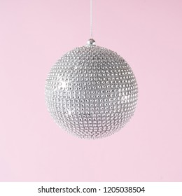 Silver shiny Christmas bauble decoration on pastel pink background. New Year party background. Minimal style.
