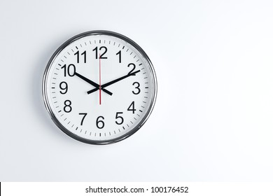 Silver shiny clock hanging at the wall with copy space