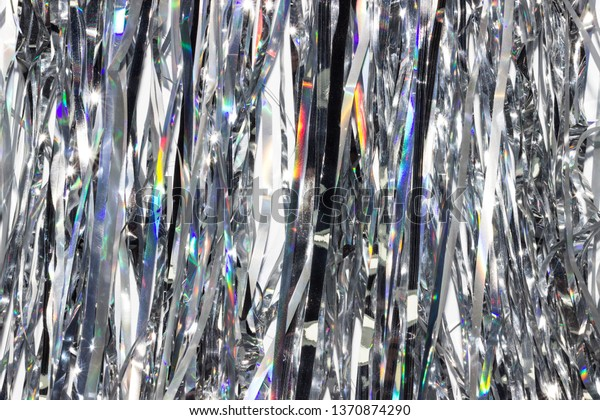 Silver shiny holographic tinsel background. Festive or party wallpaper.
